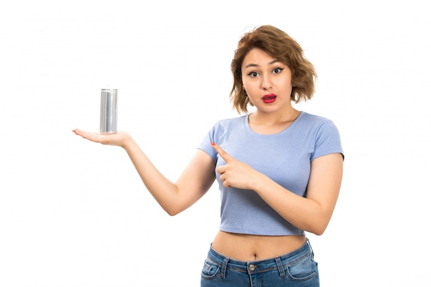 Вид спереди молодой привлекательной леди в серой футболке и синих джинсах с серебристой банкой удивляет на белом