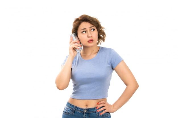 Вид спереди молодой привлекательной леди в серой футболке и синих джинсах с серебристой банкой, говорящей сквозь нее на белом