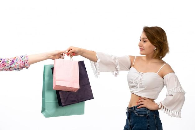 Вид спереди молодой привлекательной леди в белой рубашке и синих джинсах, делающей покупки пакеты на белом