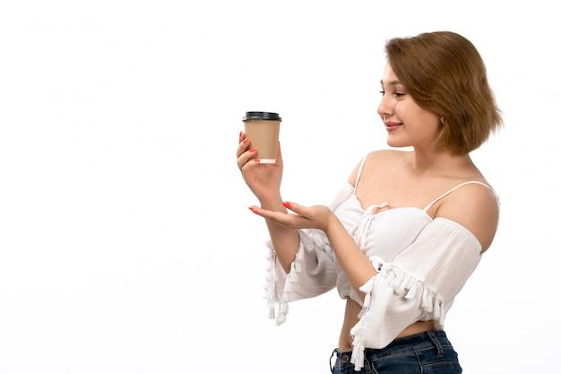 白いシャツとブルージーンズのコーヒーカップを保持している正面の若い魅力的な女性が白で笑って喜んで