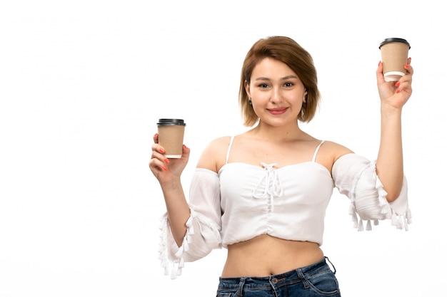 白いシャツとブルージーンズのコーヒーカップを保持している正面の若い魅力的な女性は喜んで白に笑みを浮かべて