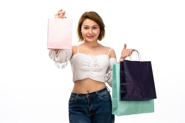 Вид спереди молодая привлекательная дама в белой рубашке и синих джинсах держит пакеты покупок на белом