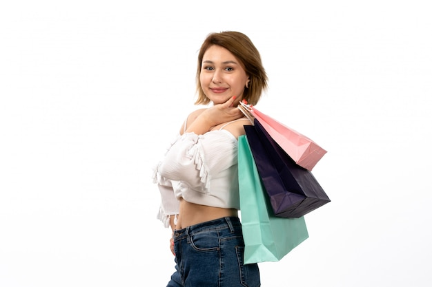 白いシャツと白に笑みを浮かべてショッピングパッケージを保持しているブルージーンズの正面の若い魅力的な女性