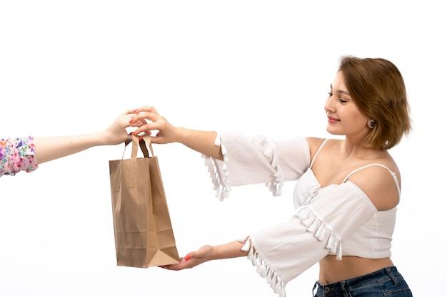 白いシャツと白に笑みを浮かべて茶色のパッケージを取るブルージーンズの正面の若い魅力的な女性
