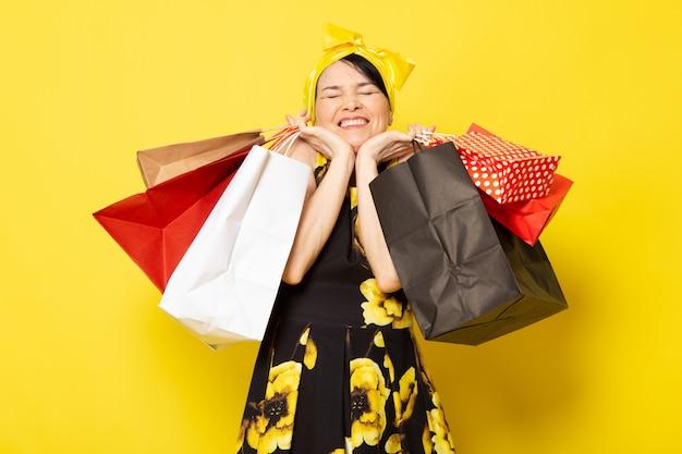 黄色の黒い花の正面の若い魅力的な女性は、黄色のショッピングパッケージを保持しているポーズの頭の上に黄色の包帯でドレスをデザインしました