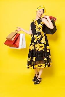 黄色の黒い花の正面の若い魅力的な女性は黄色のショッピングパッケージを保持している笑顔の頭に黄色の包帯でドレスをデザインしました