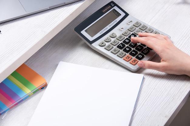 Вид спереди молодой привлекательной леди, работающей с документами перед столом с калькулятором на чашку телефона на светлом фоне работы бизнес-технологий