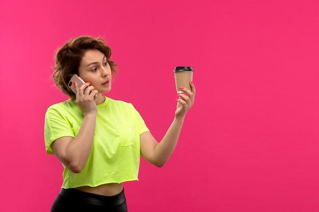 ピンクの背景の若い女性の技術にコーヒーカップを保持している電話で話している酸色のシャツ黒ズボンの正面の若い魅力的な女性