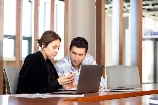 若い男が彼女のオフィスの仕事の建物の中の何かを見て電話をチェックする若い男と一緒に黒いシャツの黒いジャケットの正面の若い美しい女性実業家