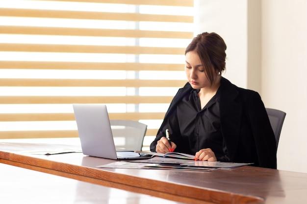 Вид спереди молодая красивая деловая женщина в черной рубашке, черный пиджак, используя ее серебряный ноутбук, написание чтения, работающих в ее офисе работа работа здания