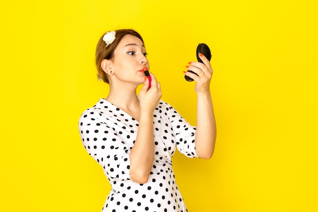 黄色の背景服ファッションマスカラブラシ口紅で化粧をしている黒と白の水玉ドレスの正面の若い美しい女性