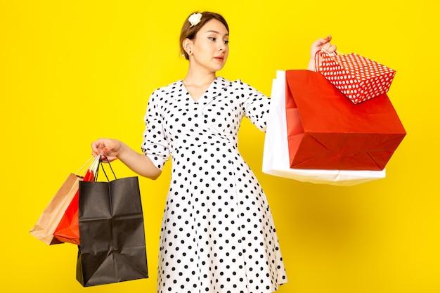 Вид спереди молодая красивая женщина в черно-белом платье в горошек, держащая пакеты с покупками на желтом