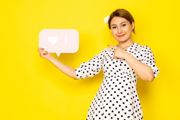 Вид спереди молодая красивая женщина в черно-белом платье в горошек держит белый, как знак на желтом