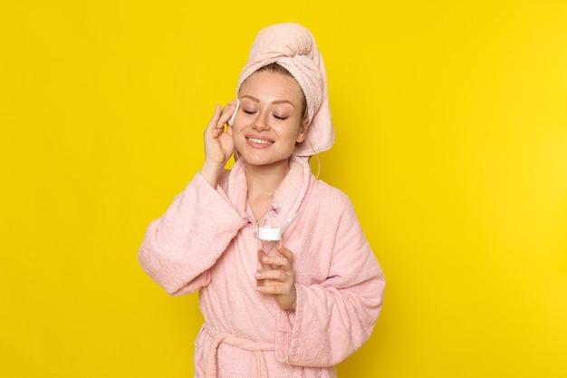 ピンクのバスローブの正面の若い美しい女性がクリーナーで彼女のすべての顔を掃除
