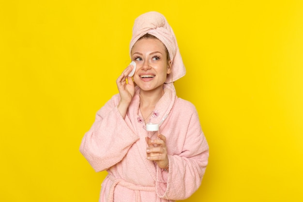 クリーナーですべての化粧をきれいにするピンクのバスローブの正面の若い美しい女性