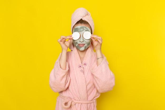 綿で彼女の目を覆っているピンクのバスローブの正面の若い美しい女性