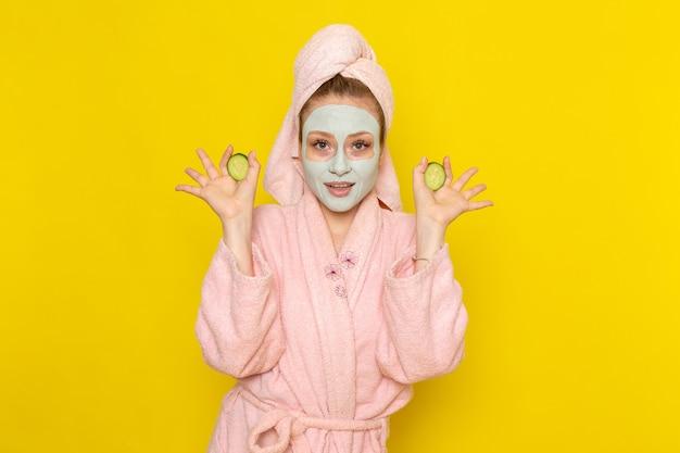 キュウリの指輪を保持しているピンクのバスローブで正面の若い美しい女性