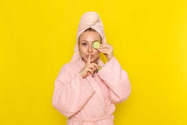 キュウリのスライスを保持しているピンクのバスローブで正面の若い美しい女性