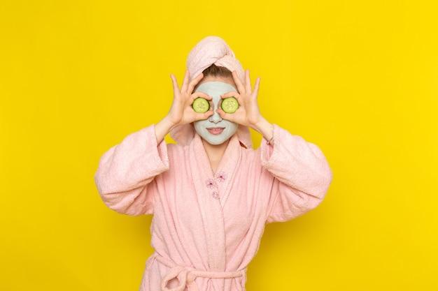 Вид спереди молодая красивая женщина в розовом халате с огурцом
