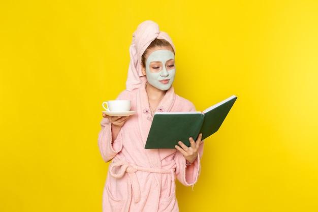 お茶と緑の本のカップを保持しているピンクのバスローブで正面の若い美しい女性