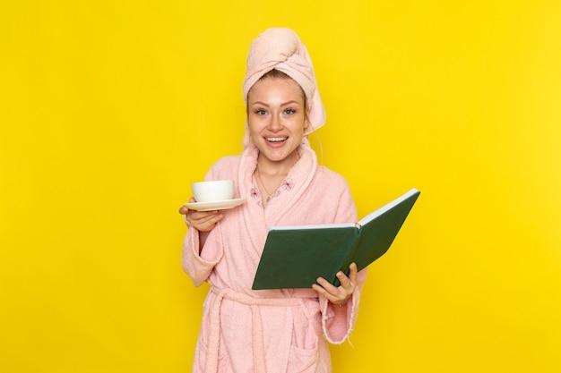 お茶と緑のお手本のカップを保持しているピンクのバスローブの正面の若い美しい女性