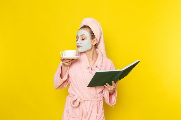 Вид спереди молодая красивая женщина в розовом халате держит зеленую книгу и чашку чая