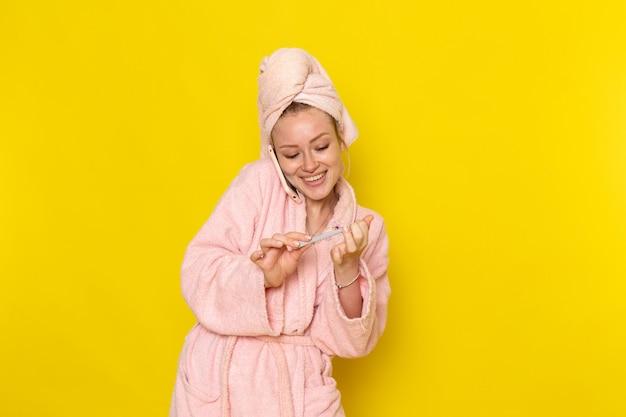 Вид спереди молодая красивая женщина в розовом халате разговаривает по телефону, поправляя ее ногти