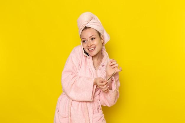 Вид спереди молодая красивая женщина в розовом халате разговаривает по телефону