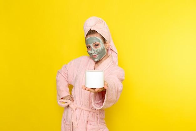 フェイスマスク保持クリームとピンクのバスローブの正面の若い美しい女性