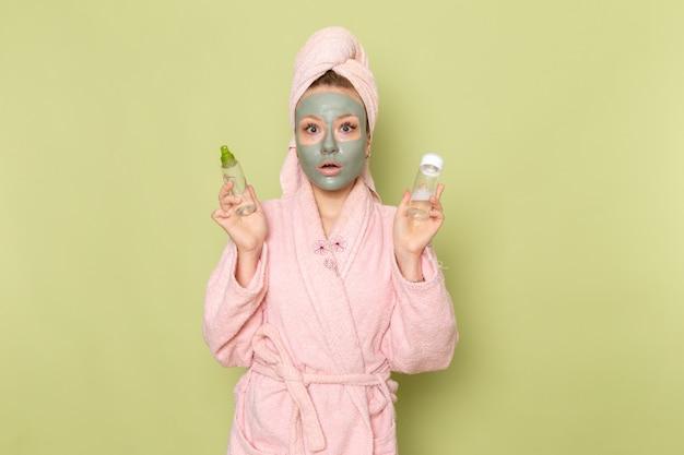 Вид спереди молодой красивой девушки в розовом халате с маской для лица, держащей колбы