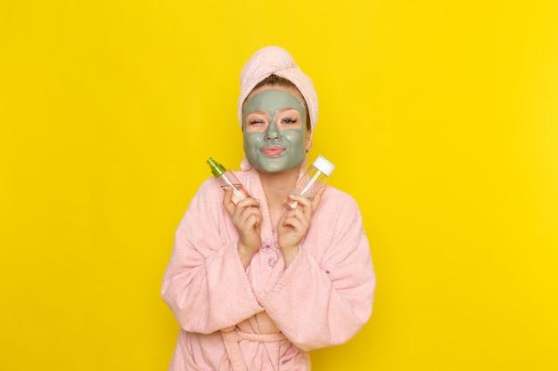 Вид спереди молодой красивой девушки в розовом халате с маской-спреем для лица