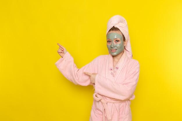 Вид спереди молодой красивой девушки в розовом халате с маской для лица