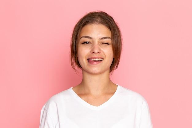 喜びと笑顔の表情でポーズをとって白いシャツの正面の若い美しい女性