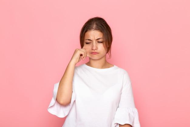 Вид спереди молодая красивая женщина в белой рубашке стягивая ее щеку