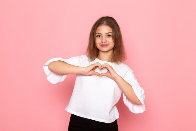 笑みを浮かべて、ハートの形を示す白いシャツの正面の若い美しい女性