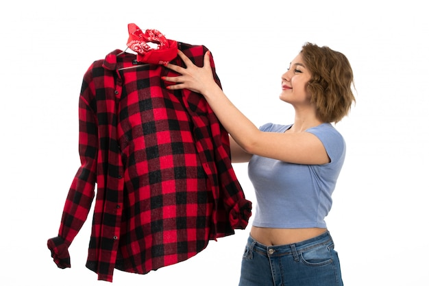 Вид спереди молодая красивая девушка в синей футболке и синих джинсах держит красно-черную клетчатую рубашку, улыбаясь на белом
