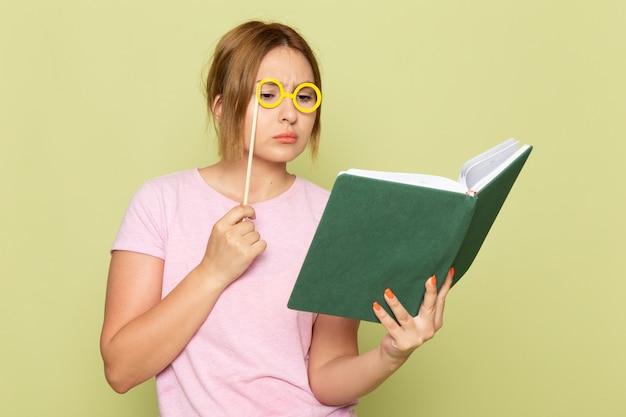 Вид спереди молодая красивая девушка в розовой футболке синих джинсах позирует с игрушечными солнцезащитными очками и читает книгу на зеленом