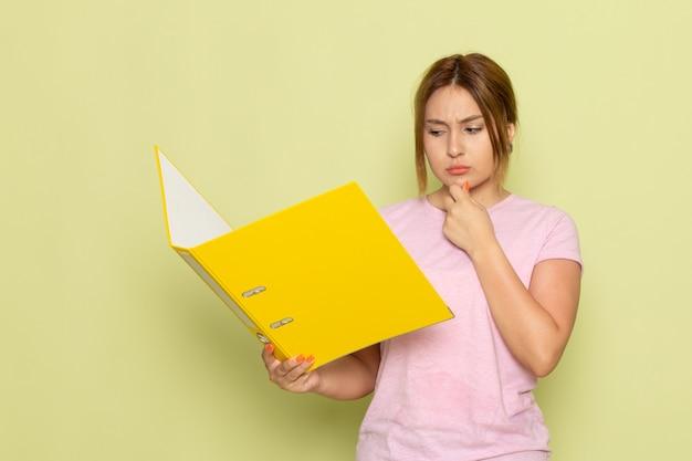 Вид спереди молодая красивая девушка в розовой футболке синих джинсах, читающая желтый файл с мыслящим выражением на зеленом