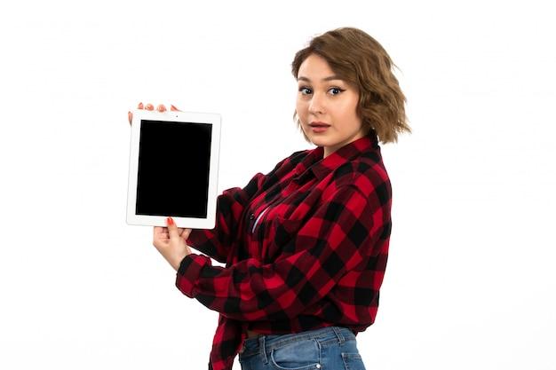 Вид спереди молодая красивая девушка в красно-черной клетчатой рубашке и синих джинсах держит белую таблетку на белом