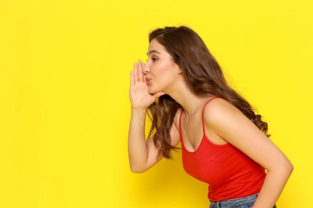 Вид спереди молодая красивая девушка в красной рубашке и синих джинсах шепчет