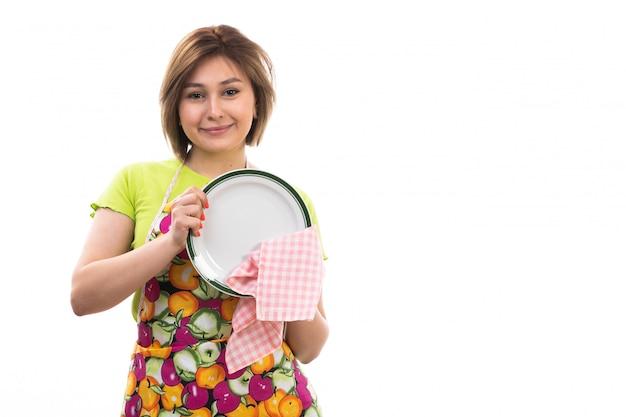흰색 배경에 집 청소 부엌에 웃 고 녹색 셔츠 화려한 케이프 청소 건조 판에 전면보기 젊은 아름다운 주부