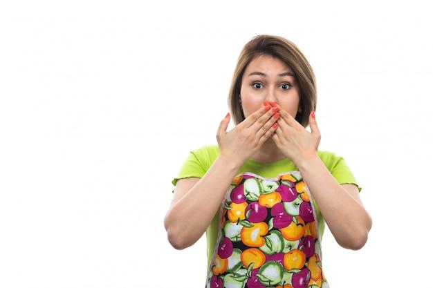 Вид спереди молодая красивая домохозяйка в зеленой рубашке разноцветной накидки закрыла рот руками шокирован выражением на белом фоне дома женской кухни