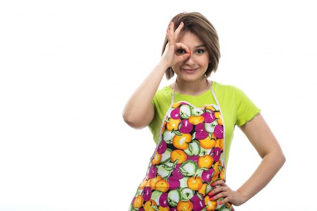Вид спереди молодая красивая домохозяйка в зеленой рубашке красочный плащ счастливой улыбкой позирует на белом фоне дома женской кухни