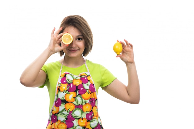 白い背景の家の女性のキッチンでスライスされたレモンで彼女の目を覆っている緑のシャツカラフルなケープを保持している正面の若い美しい主婦