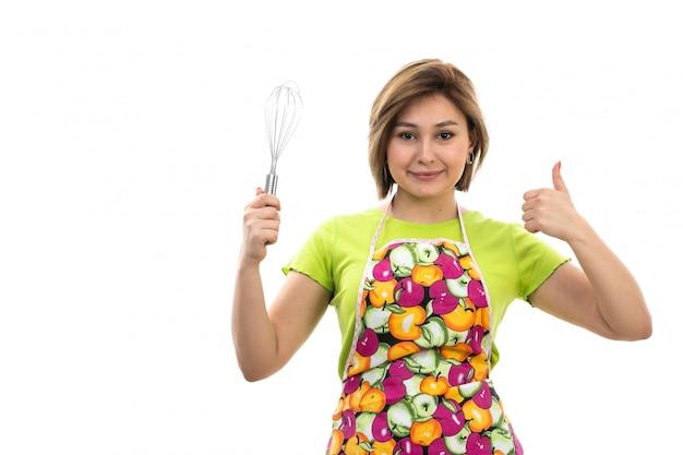 白い背景の家のクリーニングキッチンに笑みを浮かべてキッチンアプライアンスを保持している緑のシャツカラフルなケープの正面の若い美しい主婦