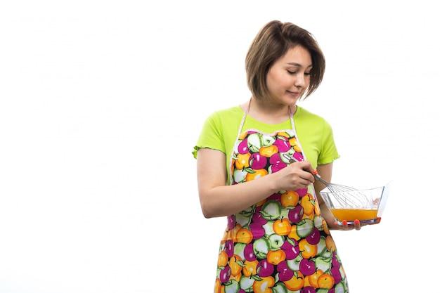 白い背景の家の女性のキッチンで食事を準備する液体の卵を混合緑のシャツカラフルなケープの正面の若い美しい主婦