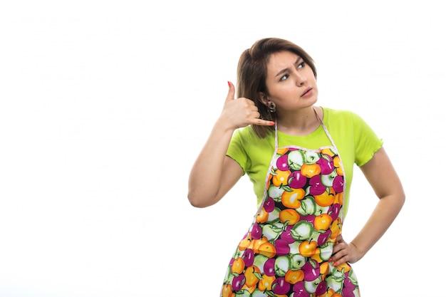 白い背景の家の女性の台所で架空の電話話を示す緑のシャツカラフルなケープのポーズで正面の若い美しい主婦
