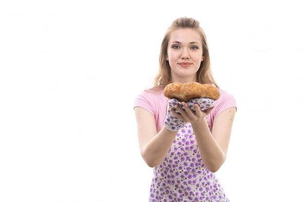 ピンクのシャツカラフルな岬幸せな笑みを浮かべて保持しているパン屋の笑顔で正面の若い美しい主婦
