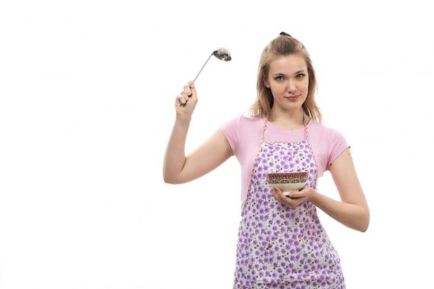 Вид спереди молодая красивая домохозяйка в розовой рубашке красочной накидке держит тарелку и серебряную ложку улыбается