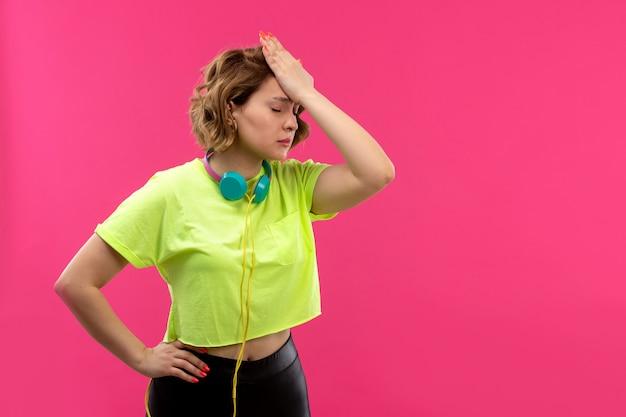 파란색 이어폰 dissapointed와 산성 컬러 셔츠 검은 바지의 전면보기 젊은 아름다운 아가씨